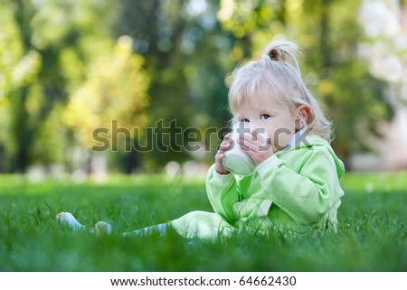A serious little girl is drinking milk on the summer meadow - stock photo