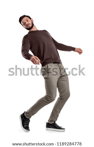 A serious looking bearded man in casual clothes stands in a half-turned view as if almost falling behind. Keeping balance. Falling back. Losing your footing.
