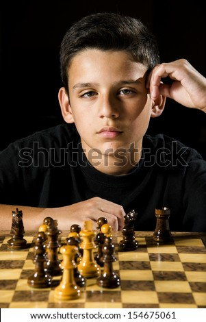 a serious looking boy stares at his opponent during a chess game.