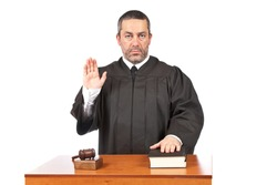 A serious male judge taking oath in a courtroom, isolated on white background. Shallow depth of field