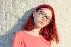 A serious teenage girl with dyed red hair, glasses and freckles. City portrait at sunset.