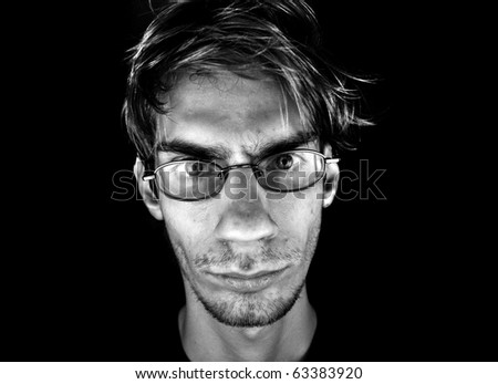 A serious white Caucasian male wearing glasses on a black background with dramatic lighting.