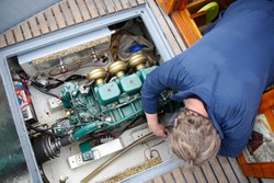 A service engineer fixing the engine of a vessel