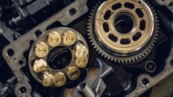 A service technician repairs a damaged hydraulic pump. Professional power hydraulics workshop. Hydraulic motor folding.