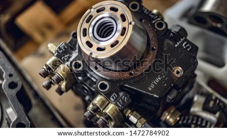 A service technician repairs a damaged hydraulic pump. Professional power hydraulics workshop. Hydraulic motor folding. Photo stock ©