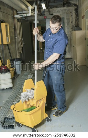 A serviceman who cleaning the floor with his mop Stock foto ©