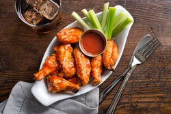 A serving of delicious spicy buffalo chicken wings on a pub style restaurant table top.