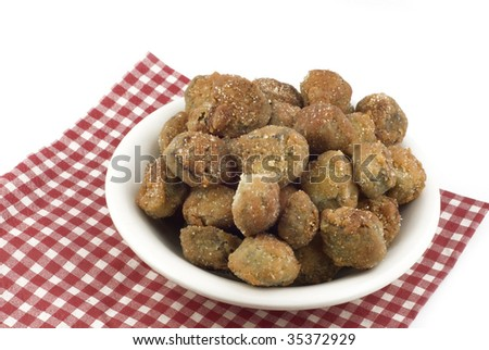 A serving of fresh sliced fried okra in a bowl on a napkin, isolated on white background with copy space