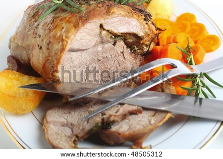 A serving plate with a joint of roasted boneless lamb roasted potatoes and boiled carrots, garnished with sprigs of rosemary with carving implements