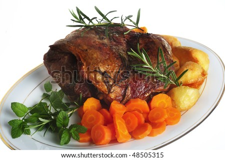 A serving plate with a joint of roasted boneless lamb roasted potatoes and boiled carrots, garnished with sprigs of rosemary and mint