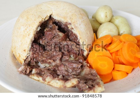 A serving plate with a steak and kidney suet pudding, boiled new potatoes and sliced carrots, a traditional English meal