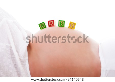 A set of baby blocks spelling out 'BABY' are balanced on the stomach of a pregnant woman. Horizontal shot. Isolated on white.