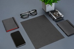 A set of black office accessories, glasses, green flower and smart on gray background