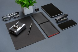 A set of black office accessories, glasses, old camera and tablet on gray background