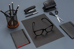 A set of black office accessories, glasses on gray background