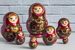 A set of bright red wooden lacquered nesting dolls on a white wooden table close up