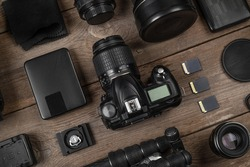 A set of camera and photographic equipment (lens, tripod, filter, memory card, hard disk) on a wood table. Professional photographer accessories background.