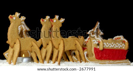 A set of Christmas gingerbread cookies on a black background - reindeer pulling a sleigh with a candle and pines.