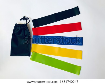 a set of colorful latex rubber bands for fitness and a black cover for them on a white background.  sports concept.  top view, flat lay, copy space