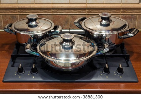 a set of cooking pots standing on kitchen stove