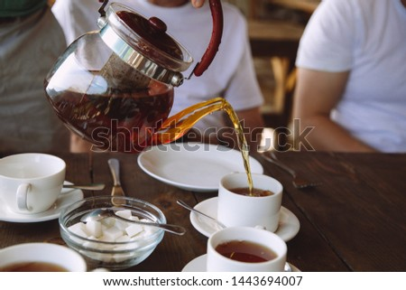 Sugar pouring into a cup of tea Images and Stock Photos