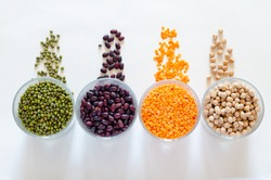 A set of different dried legumes in a glass cup and is a scattered: red lentils, mung beans, red beans, chickpeas. Flat lay, copy space.