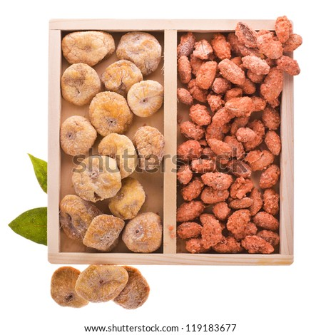 A set of dried fruit - figs and candied almonds. in a wooden box. isolated on white background