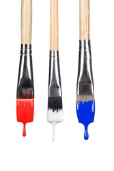 A set of dripping paint brushes with red, white and blue paint falling from the bristles.  Image was shot using real dripping paint and is not a Photoshop graphic manipulation.