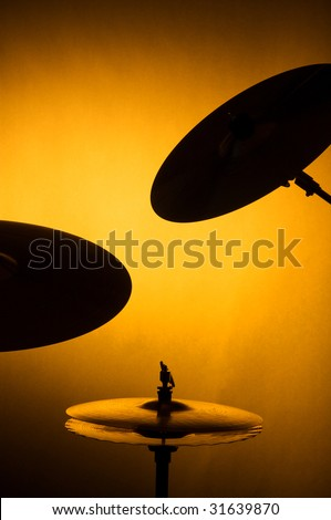 A set of drum cymbals in silhouette against a yellow gold background in the vertical format.