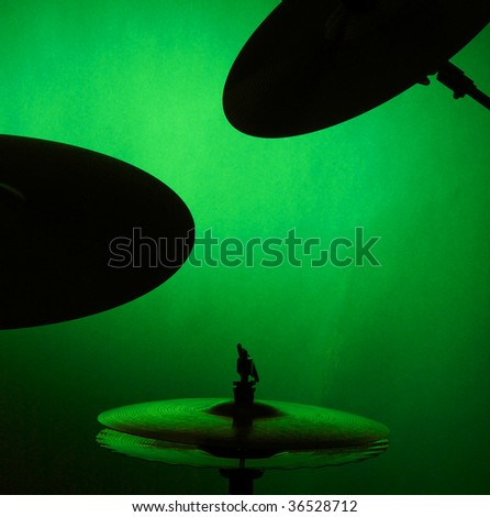 A set of drum cymbals in  silhouette isolated against a green background in the square format with copy space.