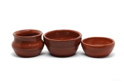 A set of earthenware (ceramic) dishes. Two earthenware bowls of different sizes and a pot, handmade in a pottery workshop. Isolated on white.