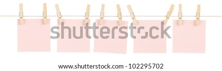 A set of five blank pink sticky notes held on a string with clothespins isolated on white.