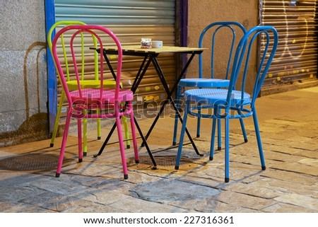 A set of four colored chairs and a small table set on the street.  On the table there is an ashtray and a small glass with a candle inside.
