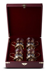 A set of four glasses with silver cup holders in finely crafted maroon, leather gift boxes