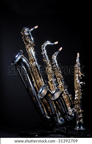 A set of four saxophones including a baritone, tenor, alto, and soprano isolated against a black background in the vertical format with copy space.