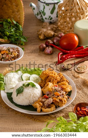 A Set of fried squid with Sambal Matah and indonesian Spicies or A set of 'Cumi Goreng Sambal Matah '. Cumi Goreng Sambal Matah is Indonesian cuisine.  Stock fotó ©