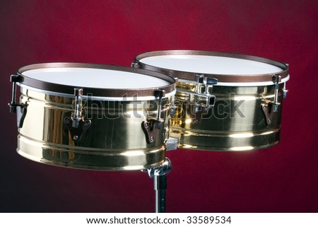 A set of gold brass timbales or bongo drums isolated against a red background. - stock photo