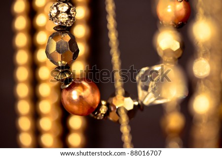 a set of golden necklaces shot at shallow depth of field on black