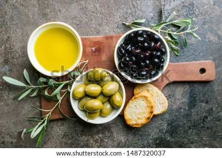 A set of Green and black olives and olive oil on a dark stone background, top view Сток-фото ©