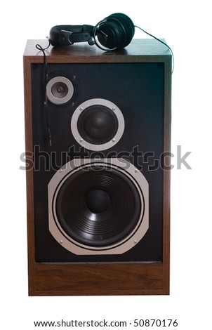 A set of headphones on a large speaker, isolated against a white background