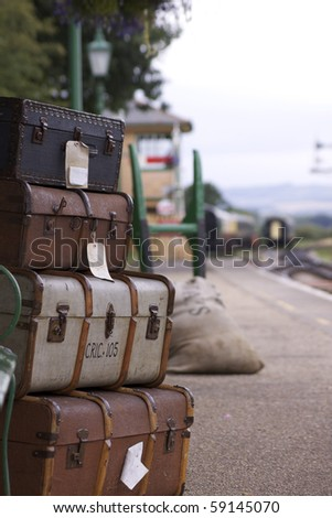 A set of labeled period luggage consisiting of old leather cases, set on a trolly on the platform of a retro railway station.