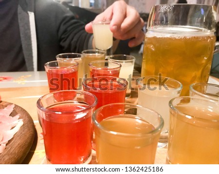A set of lots of delicious yellow orange red glasses, shots with strong alcohol, vodka, brandy, brandy, beer on wooden stands on a table in a cafe, bar, restaurant. #1362425186