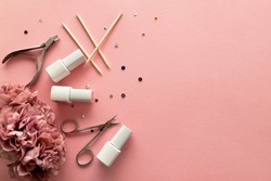 A set of manicure tools and accessories on a pink background with flowers and rhinestones. Nail care. Flat lay. Copy space. Women's Day. March 8