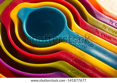 A set of measuring spoons made of colored plastic. Group of steel measuring spoons closeup, kitchen equipment.