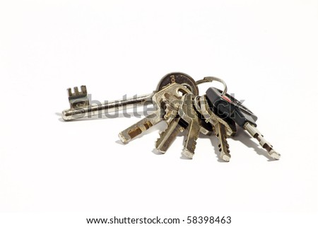 A set of metallic keys bundled in a key chain which is isolated against a white background.