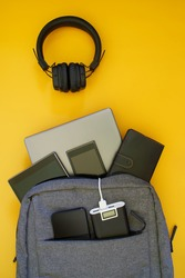 A set of modern gadgets: external battery, laptop, tablet, smartphones are in a fashionable textile backpack. Yellow background. The concept of recharging gadgets while traveling and trip. Close-up