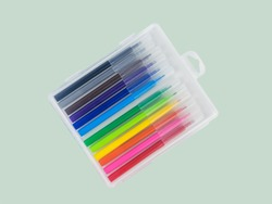 A set of multi-colored markers in a plastic box on a light background. Universal markers for school and office.