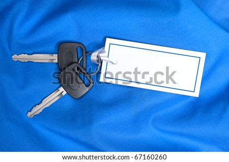 A set of new car keys with ribbon attached to a blank card for copy.  Good for Valentines Day or Christmas inferences or any inference where blue is the designers appeal.