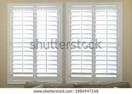 A set of open white plantation shutters in a light butter yelllow room Stock photo ©