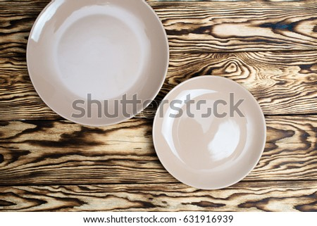 A set of plates. Empty brown plate on wooden table ストックフォト ©